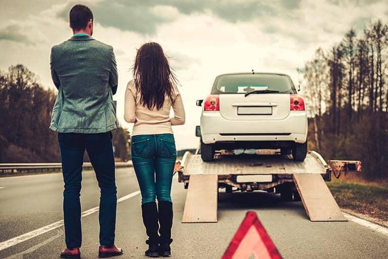couple watching their broken down car being taken away