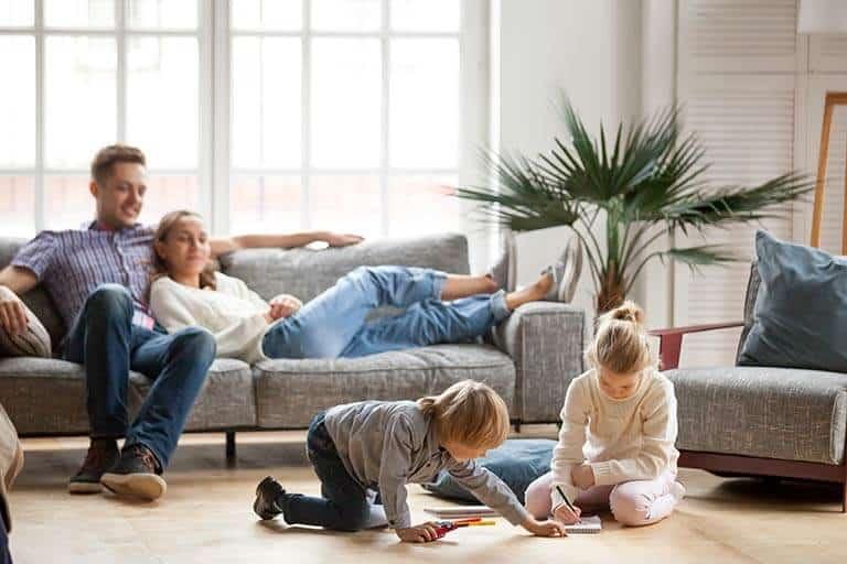 parents sat on sofa watching children play