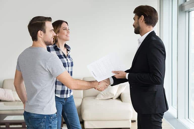 couple shaking hands with landlord over tenancy agreements