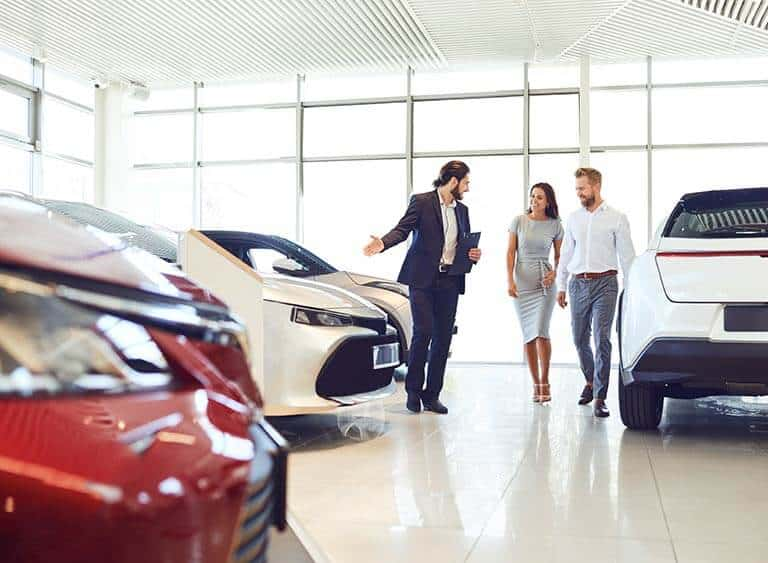car salesmen showing customers latest cars