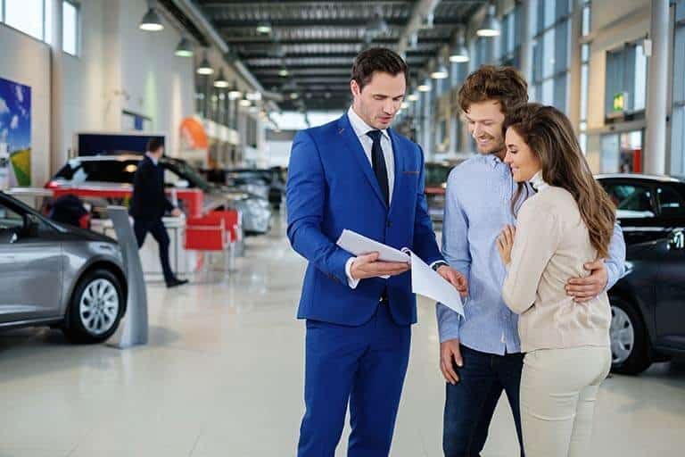 car salesmen running over details on contract with new customers