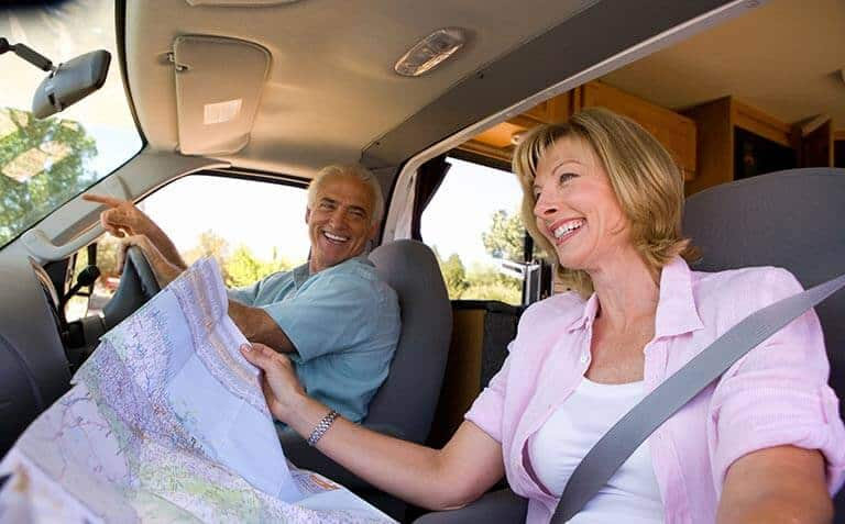 elderly couple with map driving motorhome