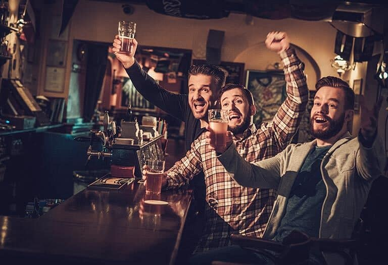 three friends cheering in the pub