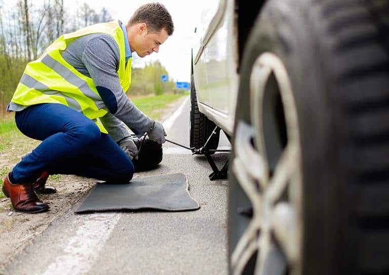 road assistance worker jacking up a broken down car