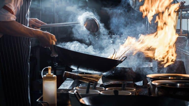 man cooking in a flaming wok