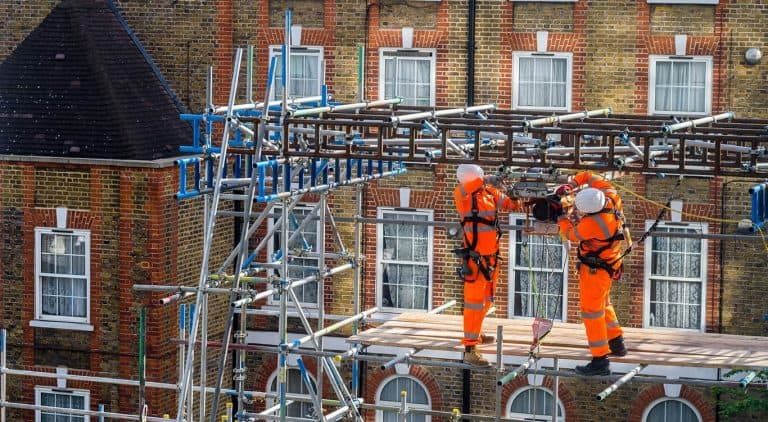pair of workers atop scaffolding
