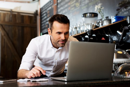 man checking laptop inside small cafe